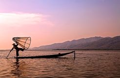 Inle Lake. Leg fishing on the Inle Lake at the sunset, Myanmar or Burma. Burmese fisherman on boat is catching fishes by traditional net stock photography