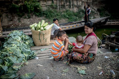 INLE LAKE, MYANMAR. (BURMA) - 22 April 2014: Local Burmese Intha woman cut and sell vegetable on a traditional open market. Local markets serves most common Royalty Free Stock Photography