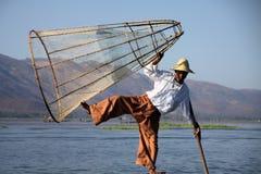INLE LAKE, MYANMAR - DECEMBER 23. 2015: Fisherman balancing on a boat with fish basket stock image