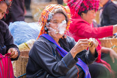 INLE LAKE, MYANMAR - December 01, 2014: an unidentified woman wi. Th cigar in traditional dress sells vegetables at market of Inn Dain Khone Village, on Inle Royalty Free Stock Images