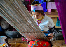 INLE LAKE, MYANMAR- SEPTEMBER 25, 2016: Padaung `long necked` woman, wearing the traditional metal rings around her neck, weaving Royalty Free Stock Photography