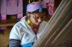 INLE LAKE, MYANMAR- SEPTEMBER 25, 2016: Padaung `long necked` woman, wearing the traditional metal rings around her neck, weaving Stock Photography
