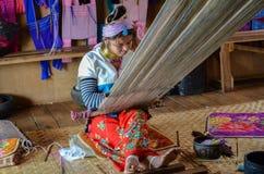 INLE LAKE, MYANMAR- SEPTEMBER 25, 2016: Padaung `long necked` woman, wearing the traditional metal rings around her neck, weaving Stock Photo