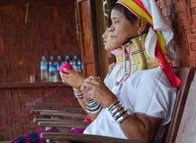 INLE LAKE, MYANMAR- SEPTEMBER 25, 2016: Padaung `long necked` woman, wearing the traditional metal rings around her neck, weaving Royalty Free Stock Images