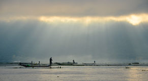 INLE LAKE, MYANMAR- SEPTEMBER 20, 2016: Silhouettes of local fisherman fishing for food at sunrise Stock Photography