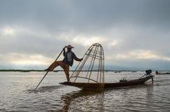 INLE, LO STATO SHAN, MYANMAR 20 SETTEMBRE 2016: Pescatore birmano tradizionale con rete da pesca nel lago Inle ad alba Fotografia Stock Libera da Diritti