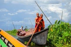INLE-SJÖ, MYANMAR SEPTEMBER 26, 2016: Buddist munkar som paddlar en pråm på Inle sjön Royaltyfri Bild