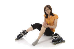 Inline łyżwiarka siedzi zdradzonego na ziemi Obrazy Stock