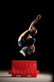Inline rider jumps. Inline rider practising at night jumping over red box Royalty Free Stock Photo