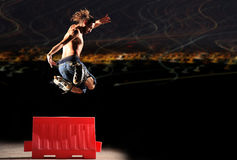 Inline rider jumps. Inline rider practising at night jumping over red box Stock Images
