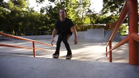Inline roller skater doing sliding from the ramp and doing a jump, bends one leg in a slow motion. Modern skate park in. The city park. Sunny, summer day stock video
