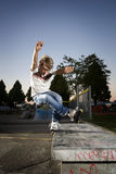 Inline Skater doing a grind on bench. During summer in skatepark Royalty Free Stock Images