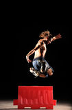 Inline Skater jumps. Inline rider practising at night jumping over red box Stock Photos