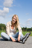 Inline skates young woman sitting asphalt road Royalty Free Stock Image