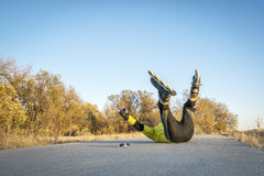 Inline skating accident. Male skater falling on concrete bike trail,late fall scenery Stock Photo