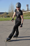 Inline Skating - Leisure Activity. Woman wearing black clothes turns left on inline skates stock photos