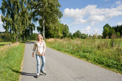 Inline skating young woman on sunny asphalt road Stock Photos