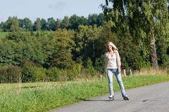 Inline skating young woman on sunny asphalt road Royalty Free Stock Photography