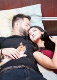 Young inlove couple on the bed with their cats Royalty Free Stock Photos