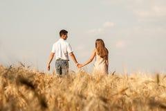 Inlove couple walking through  wheat field Stock Photo