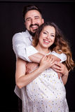 Inlove pregnant woman with her husband in studio photo Stock Photos