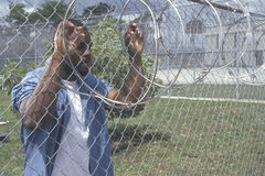 Inmate at barbed wire fence Royalty Free Stock Image