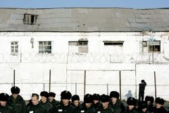 Inmates in prison. Inmates in male prison stand and wait for installation of a belfryin at the square in territory. Orthodox priests brought bell to the prison Stock Image