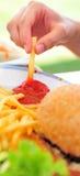 Inmersión de las patatas fritas en salsa de tomate Foto de archivo libre de regalías