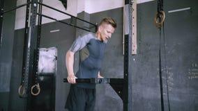 Inmersión masculina joven del tríceps que hace en un gimnasio metrajes