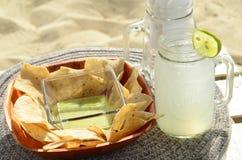 Inmersión verde de la salsa del aguacate, microprocesadores de tortilla, limonada, bocado de la playa, Baja, México Imagen de archivo