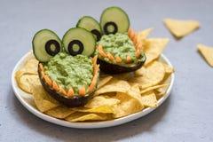 Inmersión y nachos divertidos del guacamole del aguacate del cocodrilo Imágenes de archivo libres de regalías