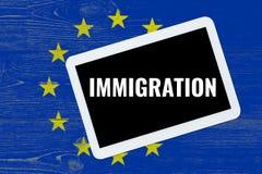Inmigración, texto en la PC de la tableta sobre bandera del eu fotos de archivo