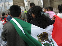 Inmigrantes que marchan en el puente de Brooklyn Imagenes de archivo