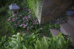 Inn garden design. A corner of the inn, flowers, lampshades, steps, and paved roads royalty free stock image