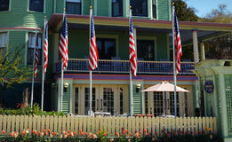 The Inn on Mackinac. A bed and breakfast, green Victorian house with six American flags flying in front on flagpoles. There are tulips blooming in front of the royalty free stock photos