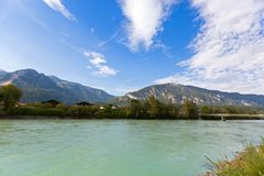 Inn river with big mountain, blue sky in background, in Rattenbe. Waterfront view of Inn river along Inn promenade with big mountain, blue sky in background, in Royalty Free Stock Photos