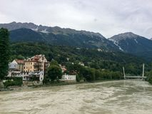 Inn river passing the city of Innsbruck with houses, mountains a royalty free stock image