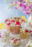Innaffi in ciotola mista con profumo ed i fiori Fotografia Stock