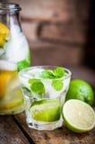 Innaffi con limetta, il limone e la menta sulla tavola di legno rustica Fotografie Stock Libere da Diritti