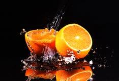 Innaffi i flussi di corrente sulle metà arancio, dinamica di un liquido fotografia stock libera da diritti
