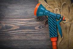 Innaffi i guanti protettivi dello spruzzatore sull'agricoltura del bordo di legno concentrata Immagine Stock Libera da Diritti