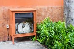 Innaffi i tubi flessibili ed il fuoco estingue l'attrezzatura Immagine Stock