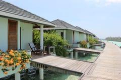 Innaffi il bungalow con i fiori e registri la passerella in Maldive Fotografia Stock