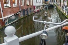 Innaffi il canale e la via con il parcheggio della bicicletta in olandese città di Delft la vecchia fotografia stock libera da diritti