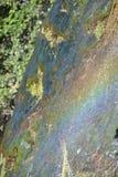 Innaffi il funzionamento su una pietra nel sunligt con effetto dell'arcobaleno Fotografie Stock Libere da Diritti