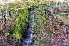 Innaffi il gocciolamento dalla parete rocciosa rossa nell'ambito di sporgenza, il muschio verde gr fotografia stock