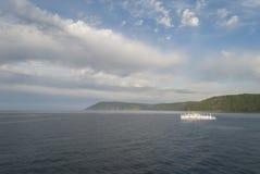 Innaffi il paesaggio con una nave, le montagne e le nuvole Fotografia Stock