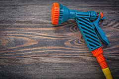 Innaffi il tubo di gomma dello spruzzatore sul concetto dell'agricoltura del bordo di legno Immagini Stock