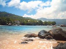Innaffi l'avvolgimento contro le rocce sull'le Seychelles tirano durante il soleggiato Fotografia Stock