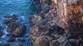 Innaffi l'increspatura in basso delle scogliere rocciose, natura selvaggia, viaggiante al litorale video d archivio